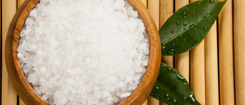 Tdva zelena lista i morska so u drvenoj činiji na podlozi od bambusawo green leaves and sea salt in wooden bowl on bamboo mat